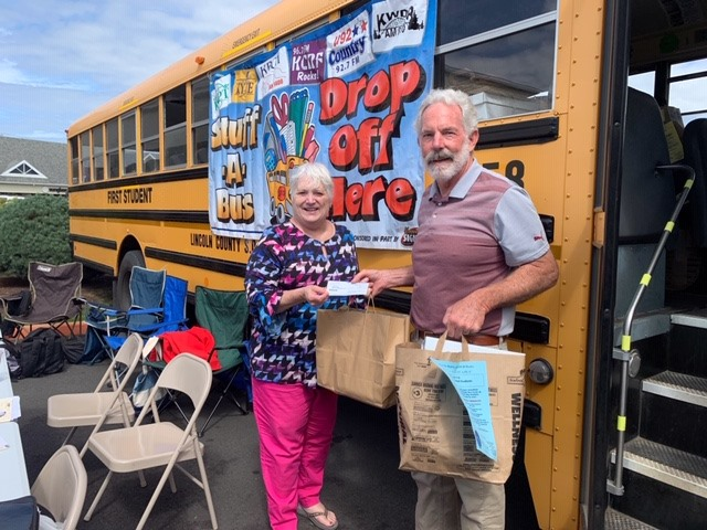 Lincoln City Mayor Dick Anderson, right, and former councilor Susan Wahlke donate a check, school supplies and peanut butter.