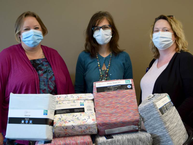 Smiling behind their facemasks with the most recently purchased sheet sets are, from left, Melissa Maxon, Patty Kinion and Theresa Karlik.