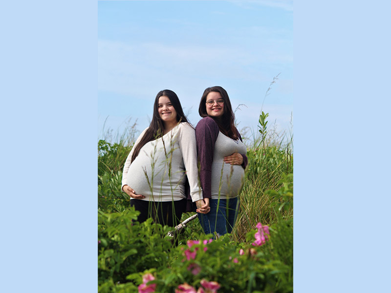 Twin sisters Tammy, left, and Tracy King pose during a maternity photo shoot.